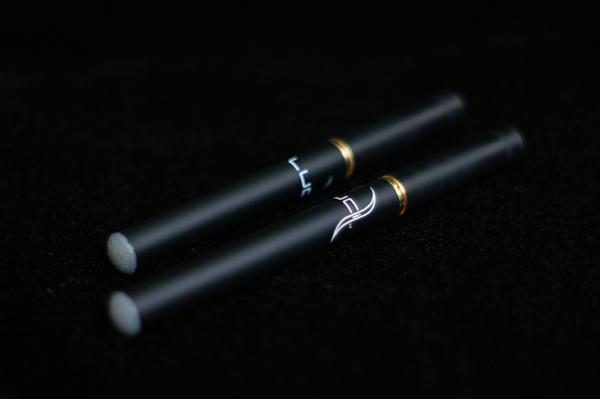 två svarta e-cigaretter med gulddetaljer i elegant reklam mot svart bakgrund